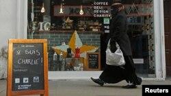 Je Suis Charlie деген жазуы бар тақтаның қасынан өтіп бара жатқан мұсылман әйел. Лондон, 14 қаңтар 2015 жыл.