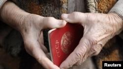 Пожилая женщина держит в руках советский паспорт. Иллюстративное фото.