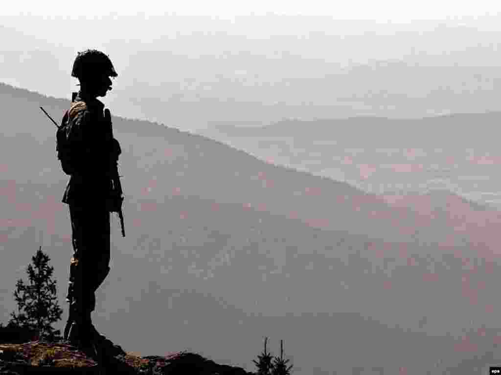 "A Pakistani Army soldier looks out over the rugged Afghan-Pakistani border from the Pakistani tribal belt - Pakistani Foreign Minister Khurshid Kasuri said in May 2007 that Islamabad is likely to remain a U.S. ally based on the need for cooperation over neighboring Afghanistan. He added that he thinks Washington understands Pakistan's ""fundamental"" role in Afghanistan's future."