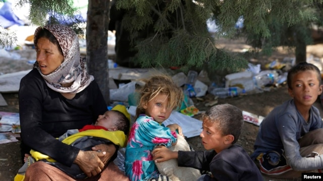 Iraq - A displaced family from the minority Yazidi sect, fleeing the violence in the Iraqi town of Sinjar, waits for food while resting at the Iraqi-Syrian border crossing in Fishkhabour, Dohuk province August 13, 2014