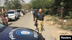 FILE: A policeman walks past a police vehicle in Karachi.