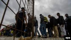 Мигранты ждут регистрации в городе Гевгелия в Македонии вблизи границы с Грецией, 7 октября 2015 года