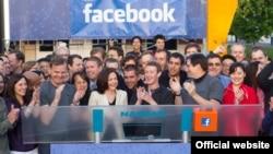 Facebook-тың бас директоры Марк Цукерберг (ортада) Nasdaq биржасына әлеуметтік желінің акциясын шығарды. (Көрнекі сурет)