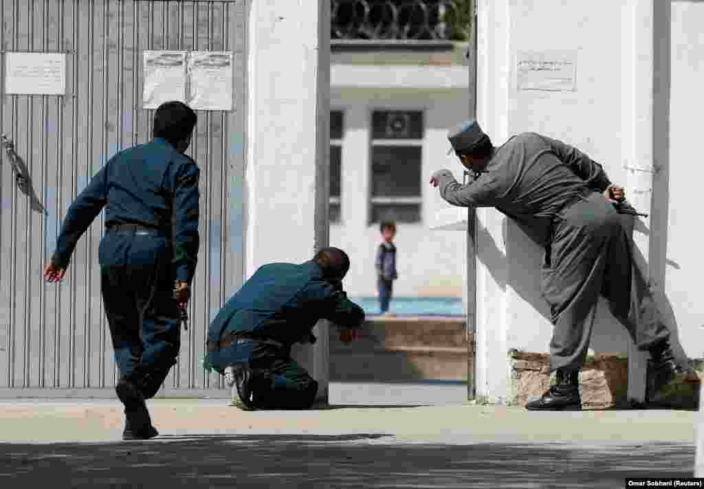 Afghan policemen try to rescue a child at the site of a suicide attack followed by a clash between Afghan forces and insurgents after an attack on a Shi'ite Muslim mosque in Kabul on August 25. (Reuters/Omar Sobhani)