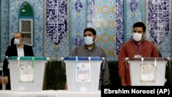 Iranian election officials wait for voters to arrive during the presidential election at a polling station in Tehran on June 18.