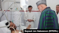 Afghan President Hamid Karzai visits blast victims in Kabul on December 7.