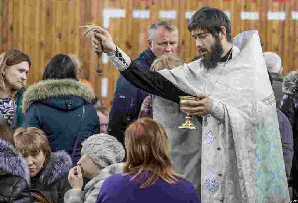 A Russian Orthodox priest conducts a requiem for the victims.