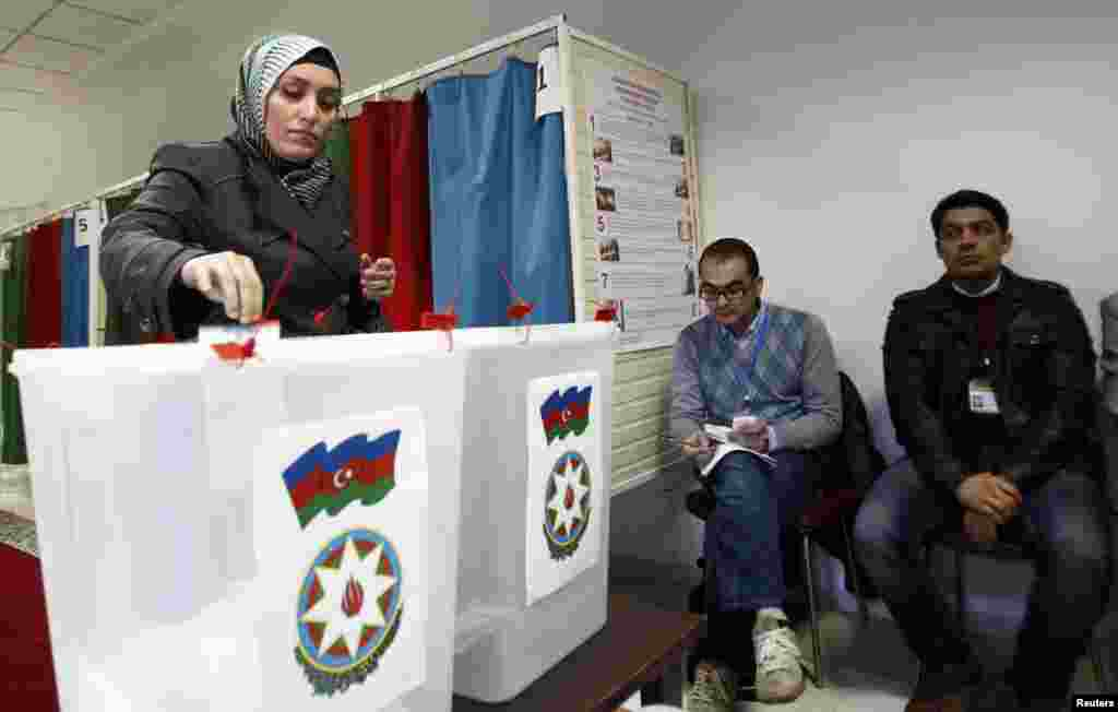 A woman casts her vote during the presidential election at a polling station in Baku.