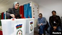 A woman casts her vote during the presidential elections at a polling station in Baku, October 9, 2013