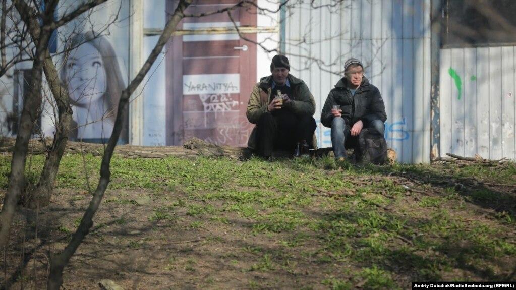 Двоє чоловіків випивають, споглядаючи на автомобільний трафік біля метро Дорогожичі