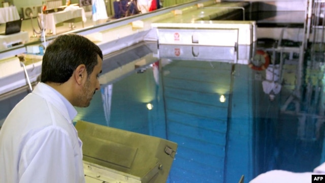 Iranian President Mahmud Ahmadinejad looks at a metal-encased rod with enriched nuclear fuel as it is inserted into a reactor in Tehran. (file photo)