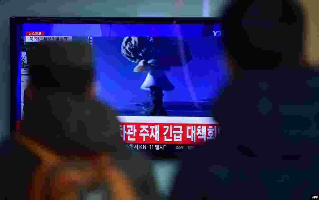 На одном из железнодорожных вокзалов Сеула люди смотрят по телевизору выпуск новостей, в котором в этот момент сообщают об испытаниях в КНДР