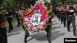 Soldiers carry wreaths and a portrait of Arsala Rahmani, a senior member of the High Peace Council who was assassinated by Afghan insurgents earlier this month.
