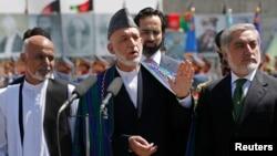 Биліктен кетіп бара жатқан Ауғанстан президенті Хамид Карзай (ортада) мен сайлауға түскен кандидаттар Абдулла Абдулла (оң жақта) және Ашраф Ғани (сол жақта). Кабул, 19 тамыз 2014 жыл.