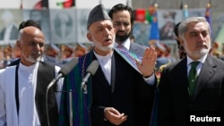 Outgoing Afghan President Hamid Karzai (center) with rival presidential candidates Abdullah Abdullah (right) and Ashraf Ghani (left) in Kabul on August 19.