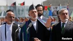 Outgoing Afghan President Hamid Karzai (center) speaks during celebrations to commemorate Afghanistan's 95th anniversary of independence as he is flanked by presidential candidates Abdullah Abdullah (right) and Ashraf Ghani in Kabul on August 19.