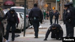U.S. -- New York Police Department (NYPD) officers search the site of a shooting in the Bronx borough of New York January 6, 2015. Two New York City plainclothes policemen were shot and wounded while responding to an armed robbery on Monday night, officia