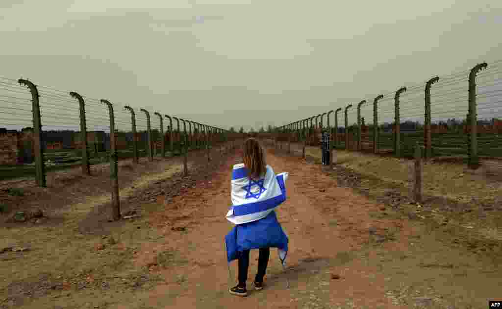 A girl with an Israeli flag stands in between barbed-wire fences at the former Nazi German Auschwitz-Birkenau death camp during the March of the Living in Oswiecim. (AFP/Janek Skarzynski)