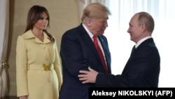 Президент России Владимир Путин (справа) и президент США Дональд Трамп пожимают руки, рядом – первая леди США Мелания Трамп, Хельсинки, 16 июля 2018 года.