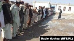 Афганские мужчины стоят в очереди у избирательного участка. 5 апреля 2014 года.