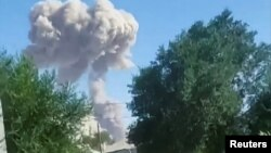 На кадре, предоставленном очевидцем, грибовидный столб дыма поднимается над районом взрывов в хранилище боеприпасов. Арысь, 24 июня 2019 года.