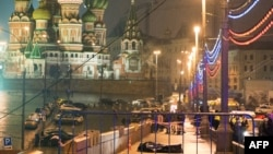 The body of Russian opposition leader Boris Nemtsov, covered with a plastic sheet, lies on Moskvoretsky Bridge near St. Basil Cathedral in central Moscow after he was killed late on February 27.