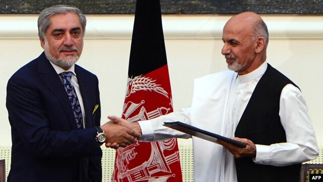 Afghan presidential candidates Abdullah Abdullah (left) and Ashraf Ghani shake hands after signing a power-sharing agreement at the Presidential Palace in  Kabul on September 21.