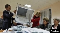 Central Election Commission staff empty a ballot box after voting closed at a polling station in the South Ossetian city of Tskhinvali on November 13.
