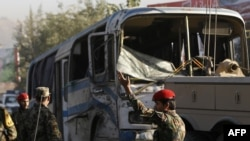 Afghan security forces inspect near an army bus at the site of a suicide attack in Kabul, October 1, 2014.