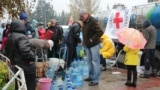 Residents of the front-line town of Toretsk, who have been without water for the past week, collect supplies from the Red Cross.