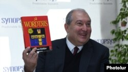 Armenia - Presidential candidate Armen Sarkissian holds a copy of a once popular video game during a visit to the Yerevan headquarters of Synopsis Armenia company, 14 February 2018.