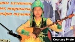 Айша Ерик в казахском национальном костюме играет на домбре. Алматы. Фото из семейного архива.