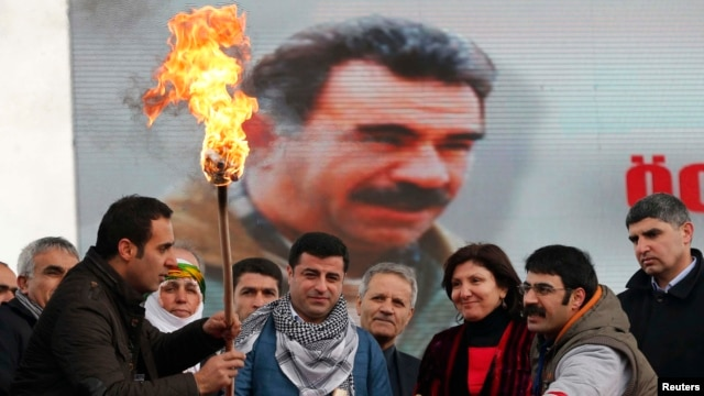 An image of militant Kurdish leader Abdullah Ocalan provides the backdrop for pro-Kurdish activists lighting a Norouz fire in Istanbul on March 17.