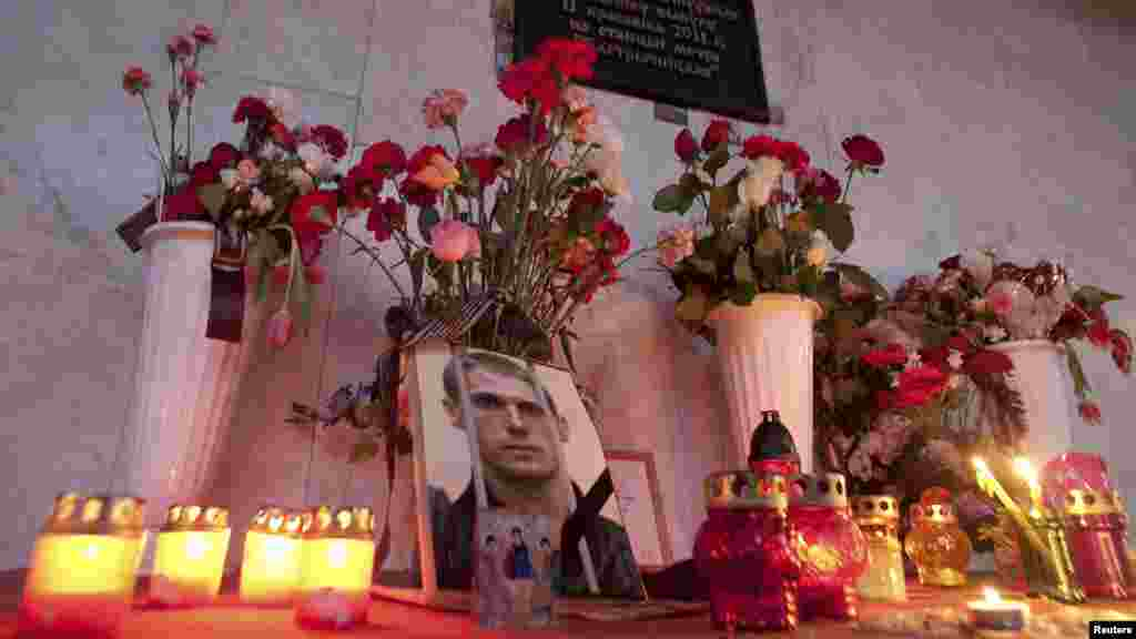 A portrait of Uladzislau Kavalyou is seen among candles and flowers at the entrance of a metro station in central Minsk on March 17. Belarus executed the two men convicted for the fatal 2011 metro bombing, despite protests from European human rights groups and calls for a retrial. (Reuters/Aleksander Vasukovich)