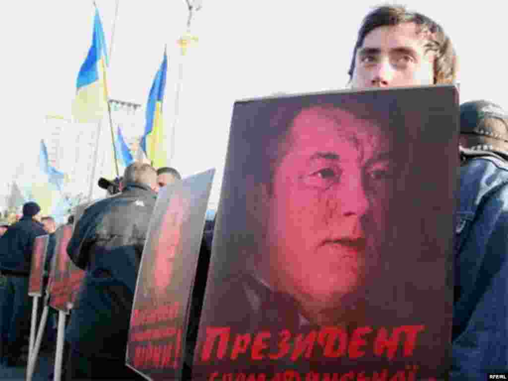"Orange Vs. Blue - A young ruling-coalition supporter holds a sign bearing a picture of President Viktor Yushchenko and reading ""Civil War President"" on April 11. (photo: RFE/RL)"