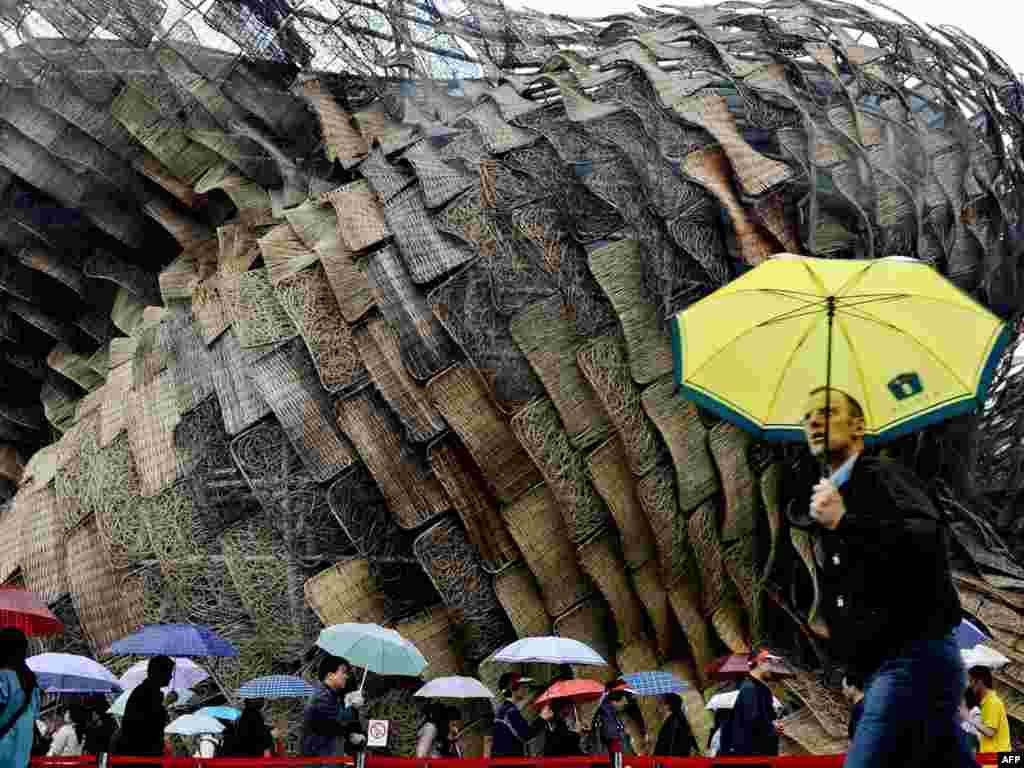 Мужчина спешит мимо испанского павильона на выставке ЭКСПО в Пекине