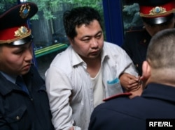 Полицейские ведут активиста оппозиции Ермека Нарымбаева в зал суда. Алматы, 2 мая 2010 года.