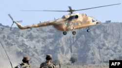 A Pakistani Army helicopter flies over soldiers in Sararogha, part of the army's offensive in South Waziristan.