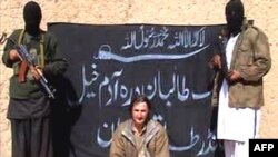 Armed Taliban militants guarding kidnapped Polish engineer Piotr Stanczak prior to executing him.