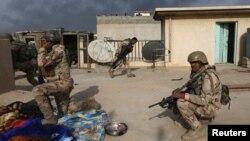 Иракские военнослужащие в укрытии во время столкновения с боевиками экстремистской группировки «Исламское государство» (ИГ). Мосул, 9 ноября 2016 года.