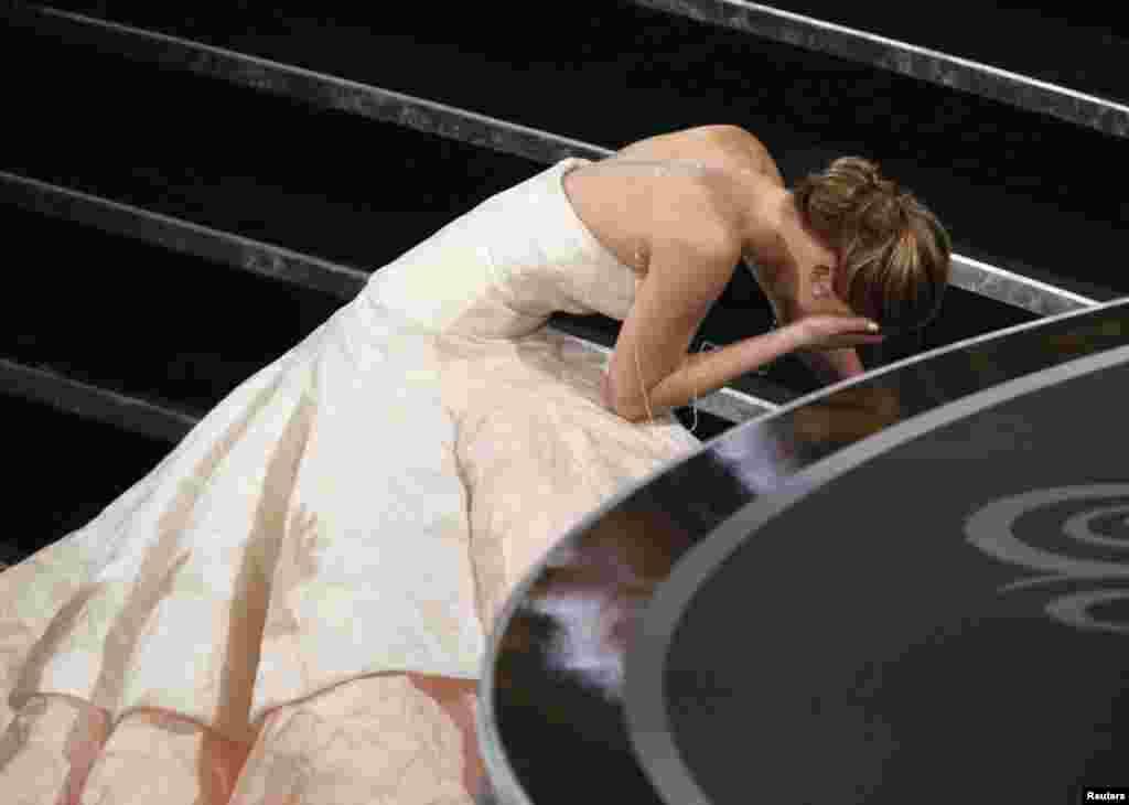 """Актриса Дженнифер Лоуренс Голливуд академиясы кино байқауында """"Silver Linings Playbook"""" фильміндегі рөлі үшін """"Ең үздік актриса сыйлығын"""" алды. Ол өзіне тиесілі сыйлықты алуға бара жатқанда баспалдаққа сүрініп жығылып қалды. (Reuters / Mario Anzuoni)"""