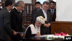 Afghan President Ashraf Ghani (C) signs a peace deal with Afghan warlord Gulbuddin Hekmatyar at the Presidential Palace in Kabul on September 29.