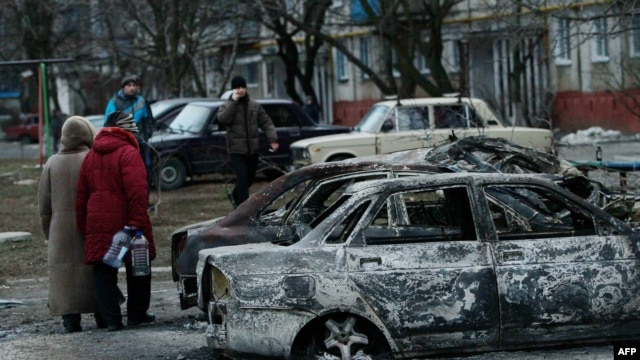 People look at burned-out cars as they walk along a street in the southern Ukrainian city of Mariupol, which was heavily shelled on January 24.