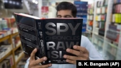 A customer in an Islamabad bookstore looks at Spy Chronicles, a new tell-all tome by former Indian and Pakistani intelligence chiefs that has caused a storm in both countries.