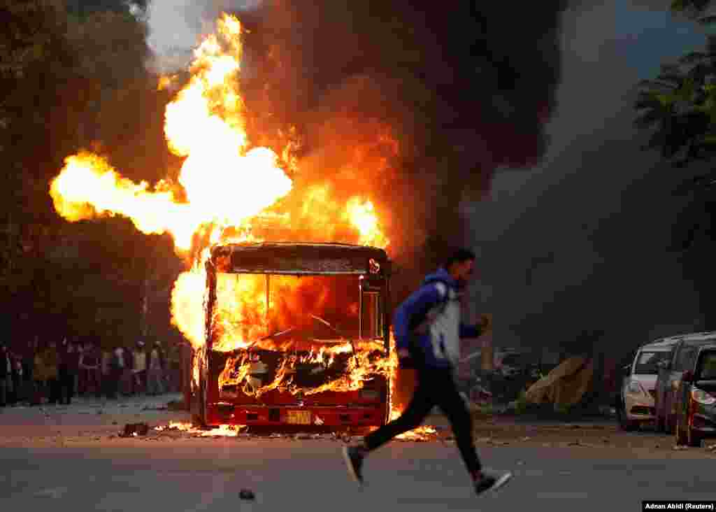 A man runs past a burning bus that was set on fire by demonstrators during a protest in New Delhi on December 15.