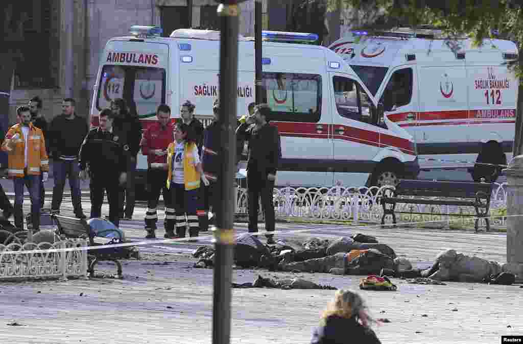 Police secure the area after the explosion, with bodies seen on the sidewalk where they fell.