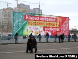 Люди проходят мимо площади, огражденной полицейскими. Астана, 22 марта 2013 года.