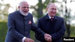 Russian President Vladimir Putin (right) and Indian Prime Minister Narendra Modi react while walking near the Constantine Palace during their meeting in St. Petersburg in June 2017.