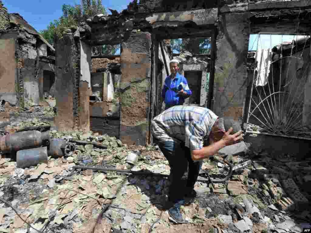 Кыйраган үйүнүн короосунда ыйлап жаткан киши. Ош. 14-июнь, 2010-жыл.