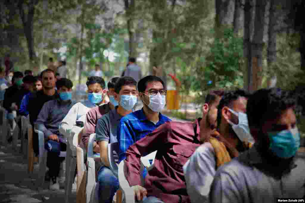 Afghan students wait to receive a dose of a COVID-19 vaccine at Kabul University on July 29.